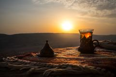 Arabian tea in glass on a eastern carpet. Eastern tea concept. Armudu traditional cup. Sunset background. Selective focus Royalty Free Stock Photos