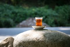 Eastern black tea in glass on a eastern carpet. Eastern tea concept. Armudu traditional cup. Sunset background. Selective focus. Eastern black tea in glass on a royalty free stock photos