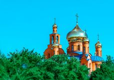 Eastern Church with gold domes or cupolas and orthodox crosses againts blue sky and green trees in Pokrov city park, Ukraine at su stock photo