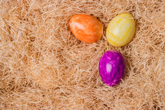 Eastern eggs. Colored Eastern eggs orange violet and yellow on straw Stock Images