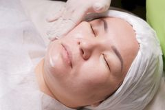 Cosmetician`s hand smears the cream on the cheek of an Asian girl. Eastern woman lies on the procedure of rejuvenation of the ski stock images