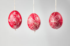 Eastern handmade traditional eggs hanging on rope. Traditional eastern eggs hanging on a rope on a gray background Royalty Free Stock Photo