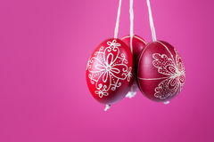 Eastern handmade traditional eggs hanging on rope. Traditional eastern eggs hanging on a rope on a pink background Stock Photo