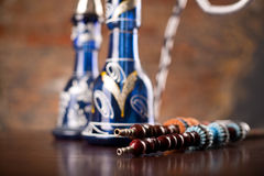Eastern hookahs on wood table. In studio close up Stock Photos