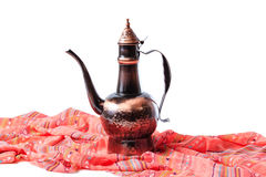 Eastern jug on a red draped cloth Stock Photos