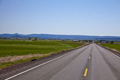 Eastern Oregon landscape. Well known Eastern Oregon landscape usually includes wide open fields, endless roads and mountains Royalty Free Stock Image