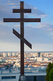 The Eastern Orthhodox Cross stand in front of Slavín war monument, and the background is huge Bratislava cityscape, skyline Stock Photo