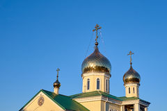 Eastern orthodox crosses on gold domes cupolas againts blue sky without clouds Stock Images