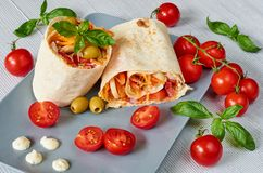 Eastern sandwich or healthy lavash snack with fresh vegetables and sauce on the gray plate decotated with cherry tomatoes, basil. Leaves. Traditional Iranian Stock Image