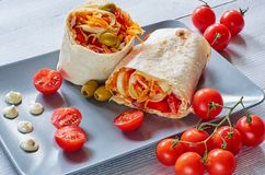 Eastern sandwich or healthy lavash snack with fresh vegetables and sauce on the gray plate decotated with cherry tomatoes, basil. Leaves. Traditional Iranian or Stock Photos