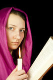 Eastern style dressed teen girl. With a candle and the Bible Stock Photos