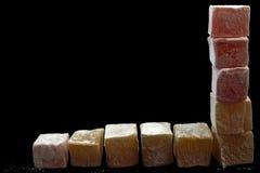 Eastern sweet. Cubes eastern sweet rahat lukum as balanced border on black Royalty Free Stock Photo