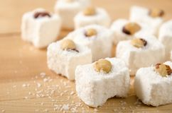 Eastern sweets, Turkish delight with coconut flakes, hazelnuts on wooden table. Eastern sweets, Turkish delight with coconut flakes, hazelnuts on a wooden table stock photos