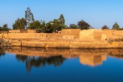 Eastern township of Ouagadougou. On a sunny day with a hole filled with rainwater in the foreground, Burkina Faso stock photos