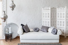 Eastern traditional interior. Morocco style room. Arch and window with beautiful carving. White and gray room with beautiful white sofa and pillows Royalty Free Stock Images