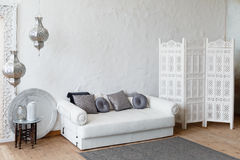 Eastern traditional interior. Morocco style room. Arch and window with beautiful carving. White and gray room with beautiful white sofa and pillows Royalty Free Stock Photos