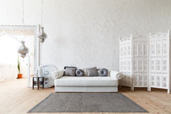 Eastern traditional interior. Morocco style room. Arch and window with beautiful carving. White and gray room with beautiful white sofa and pillows Stock Photos