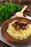 Eastern traditional wheat porridge - bulgur with roasted pieces fatty meats, bacon in a clay bowl Stock Photos