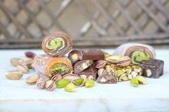 Eastern Turkish sweets with pistachios on white wooden background. Fragrant baklava, chocolate, sweets with pistachios royalty free stock photo