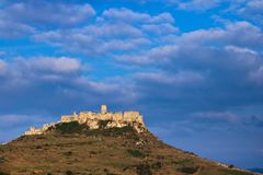 View of the Spis castle from the east at sunrise with cloudy weather in early spring. A eastern view of the Spis castle taken from a nearby field at sunrise in stock photography