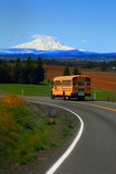 Eastern Washington. A road meandering through beautiful eastern Washington state, with a school bus. Snow capped Mt Adams in the Gifford Pinchot National Forest Stock Photography