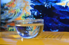 Eastern and western. Cup of water on a traditional Chinese book with background of a western painting royalty free stock images