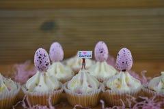 Eastertime杯形蛋糕用鸡蛋和拿着标志的一个微型人小雕象表明i爱复活节 库存照片