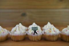 Eastertime cupcakes με ένα μικροσκοπικό ειδώλιο προσώπων που κρατά ένα σημάδι για ευτυχές Πάσχα Στοκ φωτογραφία με δικαίωμα ελεύθερης χρήσης