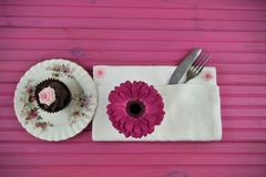Easter time table place setting with chocolate cupcake and fresh flowers. Eastertime or springtime table place setting with floral plate a white napkin and knife Stock Photography