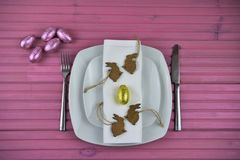 Pink Easter time table place setting in white with chocolate wrapped eggs and rabbit shape decorations royalty free stock photo