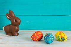 Eastet koloru jajka obok czekoladowego Wielkanocnego królika na błękitnym drewnianym tle zdjęcia stock
