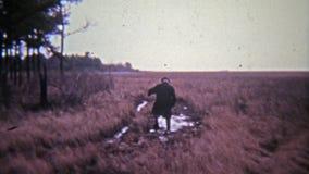 EASTON, MARYLAND 1972: Viejo hombre que camina a través de charco de fango en campo de hierba abierto almacen de metraje de vídeo