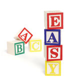 Easy ABC Blocks. Four wooden alphabet blocks on white background, stacked to form the word, 'easy'. ABC blocks are out of focus in background. Blocks cast stock image