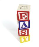 Easy Alphabet Block Stack. Four wooden alphabet blocks on white background, stacked to form the word, 'easy'. Stack of blocks casts a shadow Royalty Free Stock Image
