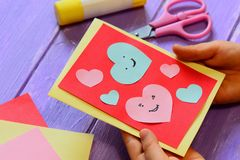 Child is holding a Valentines card in his hands. Child is showing a greeting card. Happy Valentines Day card. Easy paper crafts. Easy art and craft with paper royalty free stock image