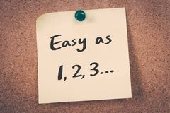 Easy as 1 2 3. Concept reminder message on a cork board royalty free stock images