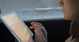 Easy chatting in car using tablet PC. Close-up shot of a woman traveling by car on cold dull day. She using touch pad to chat during the trip stock footage
