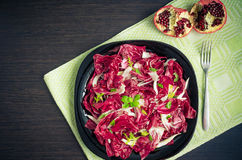 Easy diet chicory salad with pomegranate. On dark wooden background with fork. Italian bitter red chicory radicchio salad. Vegetarian Food. Healthy food Stock Photos