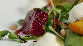Easy diet salad with raw beets close up. Useful strawberry salad with arugula nuts and honey on the white plate. Fresh stock video footage