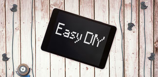 Easy diy against tablet pc on wooden surface Royalty Free Stock Image
