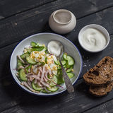 Easy and fast salad with smoked turkey, cucumber and boiled egg on a dark wooden background. Stock Image