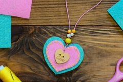 Easy felt heart pendant necklace. Valentines day felt pendant necklace with beads and wooden button. Kids creative workplace. Kids art workplace. Gift for mum royalty free stock photo