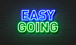 Easy going neon sign on brick wall background. Royalty Free Stock Photos