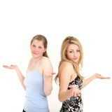 Easy going women shrugging in indifference. Two pretty easy going women shrugging their shoulders and raising their hands in indifference or ignorance Stock Photos