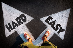 Easy or hard. Red sheoes from above on the white arrows signs for hard and easy way,dilemmas concept Stock Images