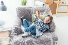 Easy home improvement. Boy sitting on an armchair covered with a protective plastic sheet and holding a paint roller, home improvement and renovation concept Stock Images