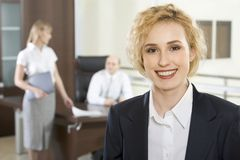 Easy job. Portrait of pretty smiling businesswoman in the office and two businesspeople on the background Stock Photo