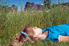 Easy Listening. Young girl listening to music in daisy field royalty free stock image
