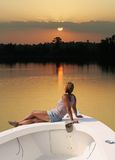 Easy Living. Peaceful scene of a woman sitting on a boat watching the sun come up Stock Image