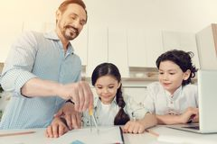 Happy clever man helping his kids with homework Royalty Free Stock Photo